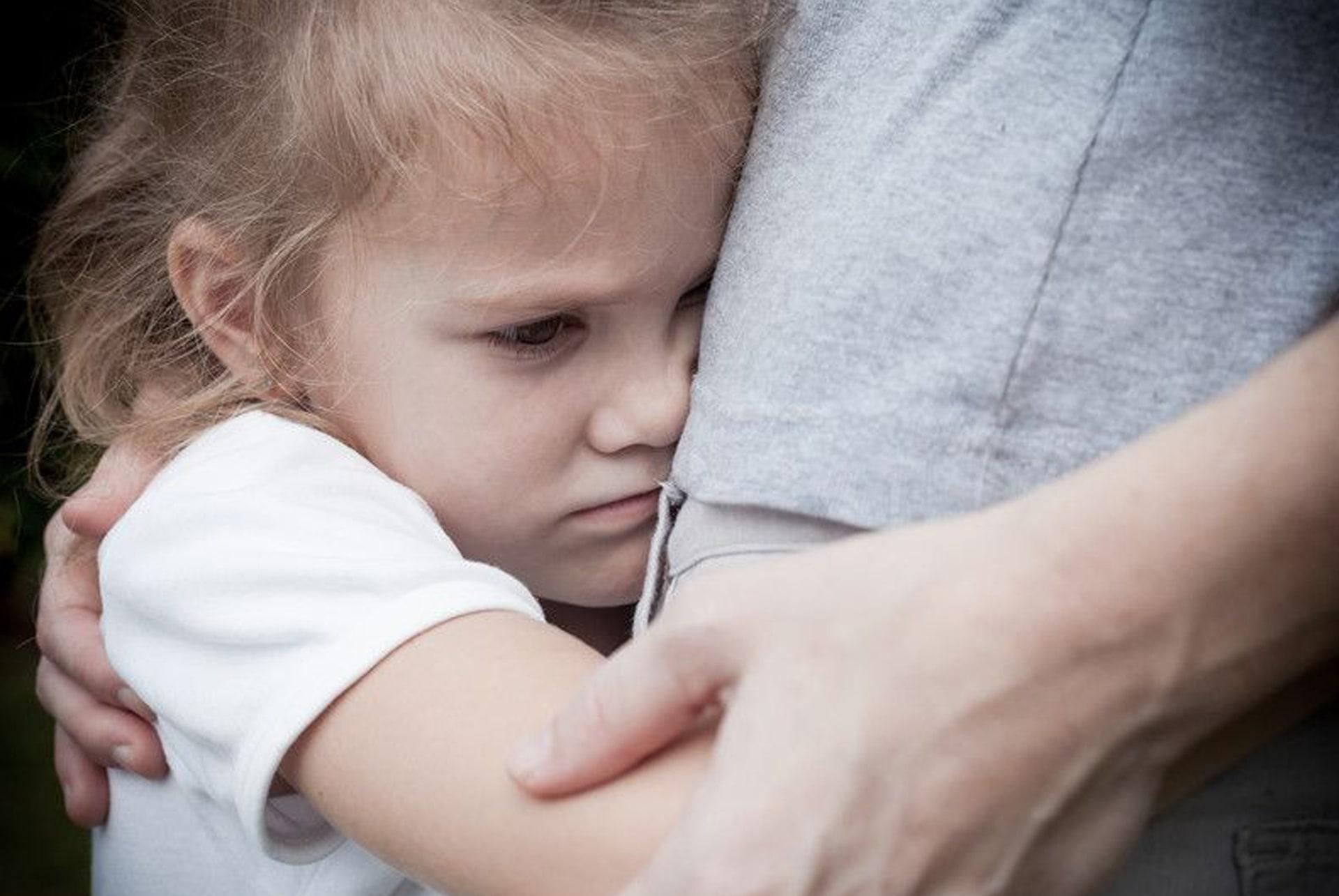 Niña menor abrazada a un progenitor